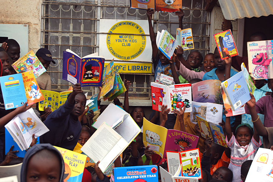 Kids show off their favorite books at The Hope Library, Kibera slum, Nairobi, Kenya